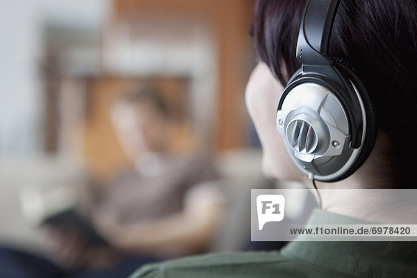 Close-up of Woman Wearing Headphones  Man Reading in the Background