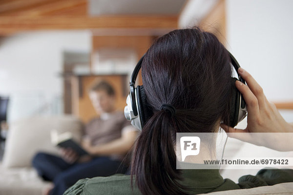 Back View of Woman Wearing Headphones  Man Reading in the Background