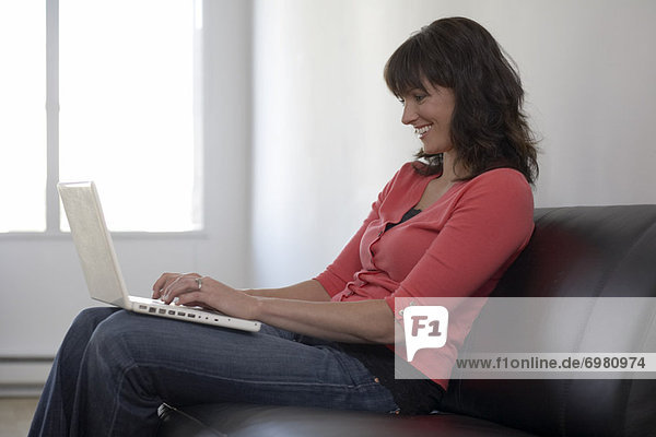 Woman Sitting on Sofa Using Laptop Computer