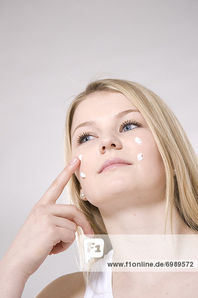 Woman Applying Skin Cream to Face