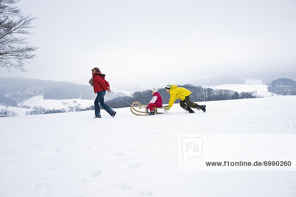 Mother Pulling Daughter in Sled  Son Pushing Sled from Behind