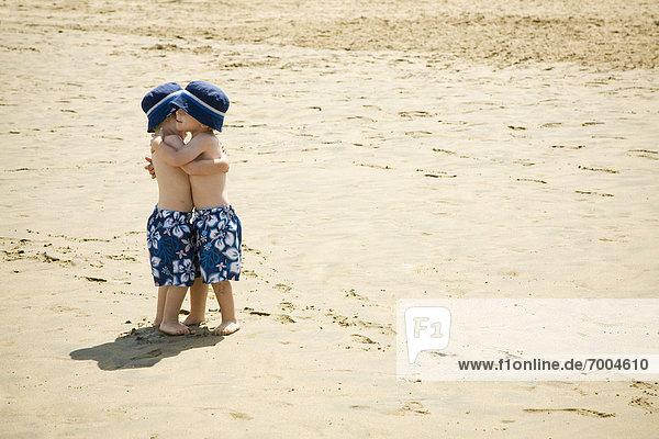 Twin Boys Hugging on Beach