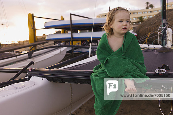 Portrait of Young Girl Wrapped in Towel Sitting on Mast of Sailboat
