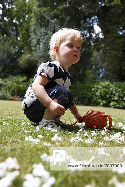 Baby Girl Crouching on Grass in Garden  Farnham  England