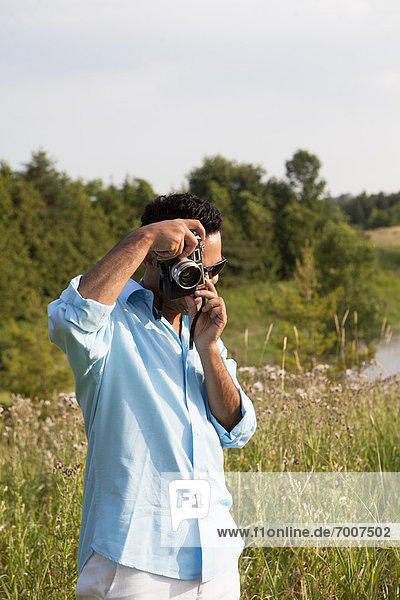 Man Taking Picture with Vintage Camera  Ontario  Canada