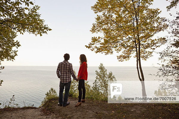 Backview of Young Couple Standing at Edge of Cliff Looking out at View  Ontario  Canada
