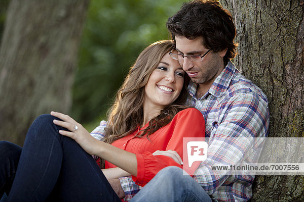 Close-up Portrait of Young Couple Sitting in Park