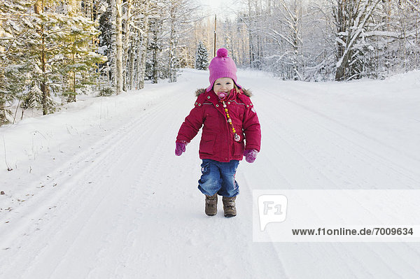 Portrait of Little Girl Walking Down Road in Winter