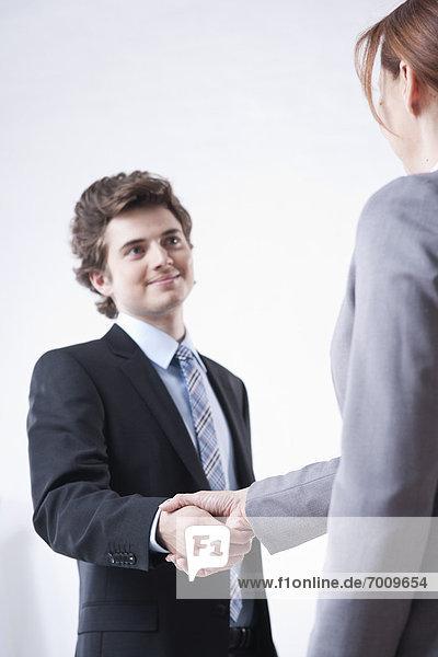 Geschäftsfrau  Geschäftsmann  jung  schütteln