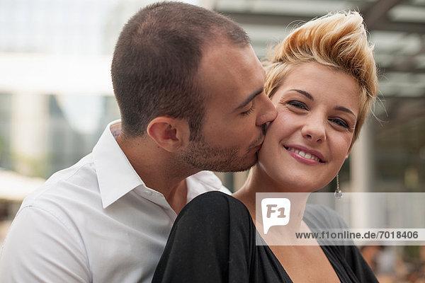 Lächelndes Paar beim Küssen im Freien