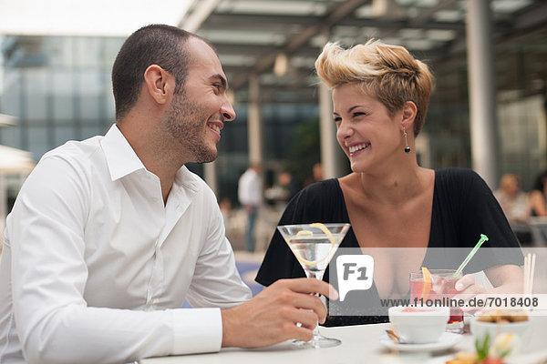 Lächelndes Paar bei einem Drink im Freien