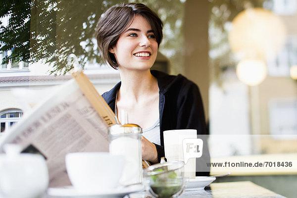 Frau liest Zeitung im Café