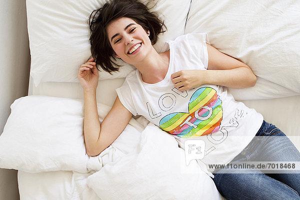 Lächelnde Frau entspannt auf dem Bett