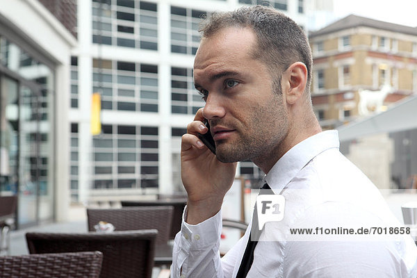 Businessman on cell phone at cafe