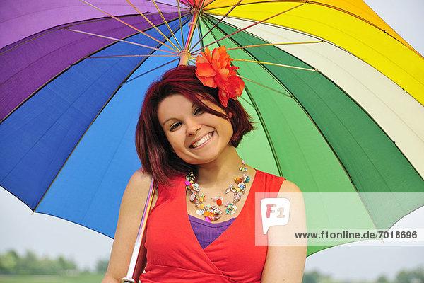 Frau mit farbenfrohem Regenschirm