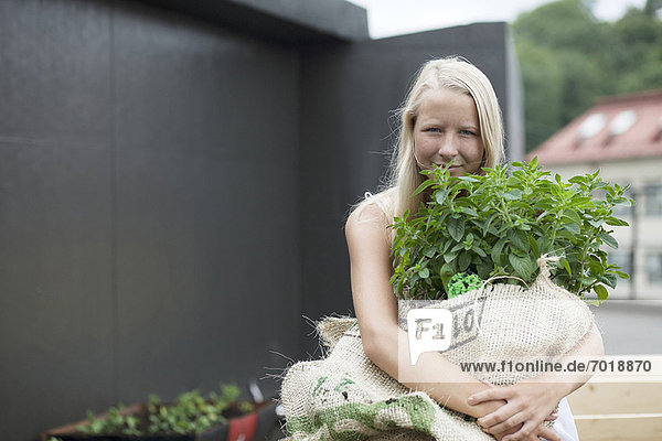 Teenagermädchen mit Pflanzensack