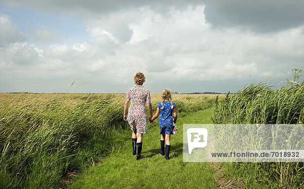 Mutter und Tochter beim Spaziergang auf dem Feld