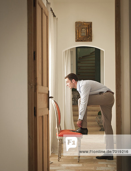 Businessman tying his shoe in home