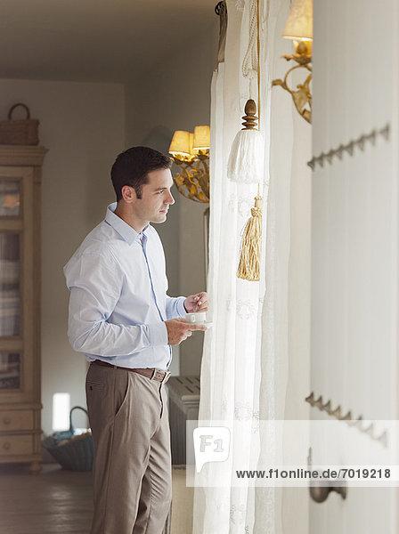 Businessman standing at window