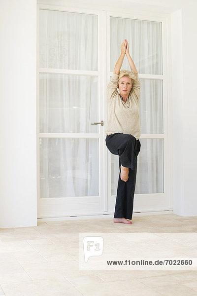 Ältere Frau beim Yoga auf der Dachterrasse