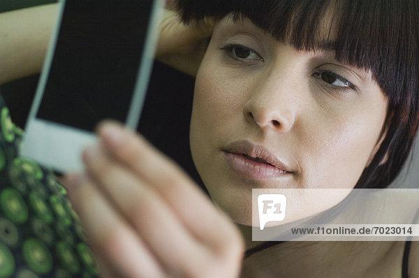 Woman looking sadly at photograph