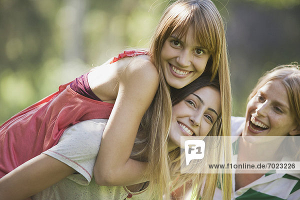 Young woman giving girlfriend piggyback ride