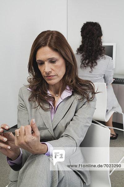 Geschäftsfrau  die ihre Nägel bei der Arbeit feilt