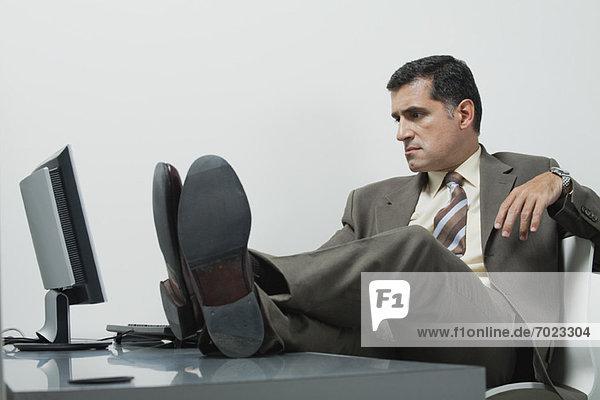 Geschäftsmann sitzend im Büro mit Füßen auf dem Schreibtisch