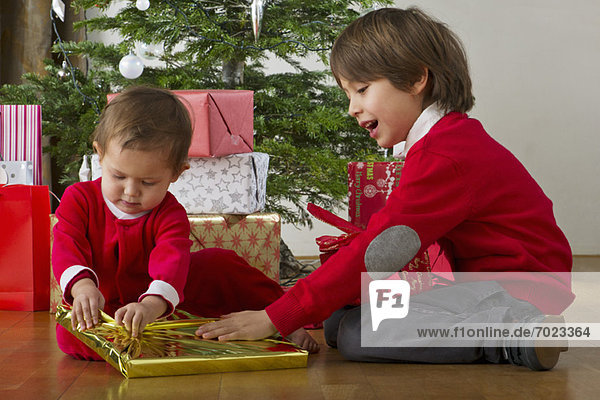 Boy helping his baby sister open Christmas presents