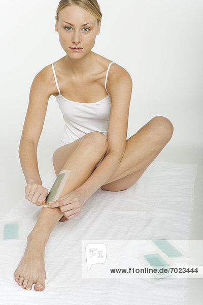 Junge Frau beim Wachsen der Beine mit Kaltwachsstreifen