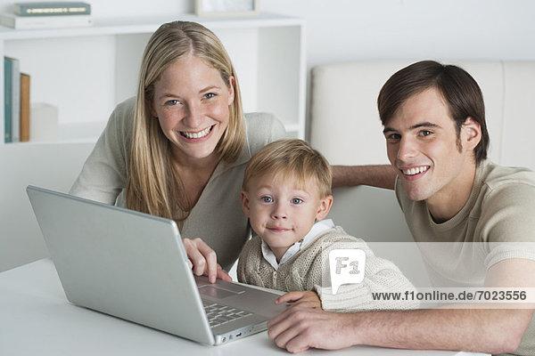 Junge Eltern und kleiner Junge mit Laptop  Portrait