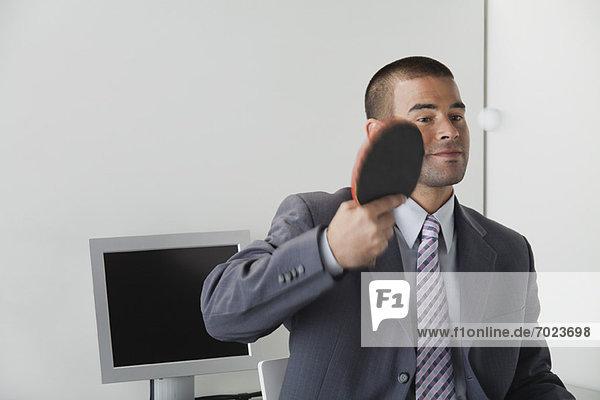 Junger Mann spielt Tischtennis im Büro