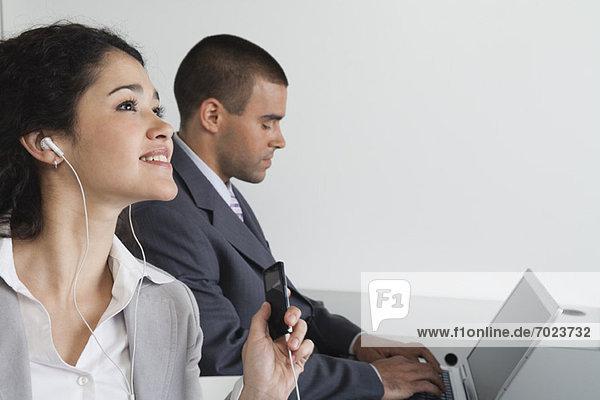 Junge Frau hört MP3-Player im Büro