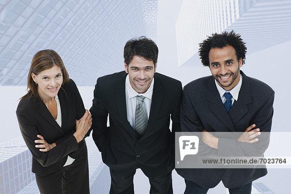 Team von Führungskräften lächelt selbstbewusst mit Wolkenkratzern auf dem Hintergrund