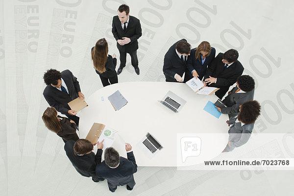 Geschäftsfreunde im Meeting  die auf dem überlagerten Bild von hundert Euro-Banknoten stehen