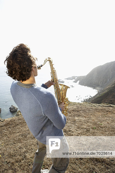Man playing saxophone on cliff (rear view)