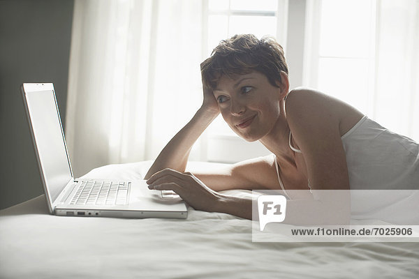 Mid adult woman using laptop on bed