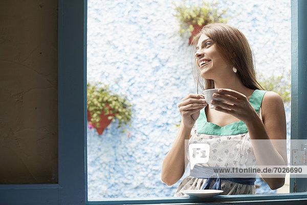 Woman drinking tea at window