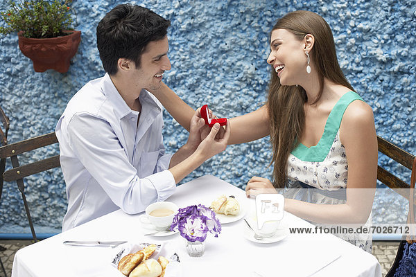 Man proposing woman in restaurant  woman touching his face