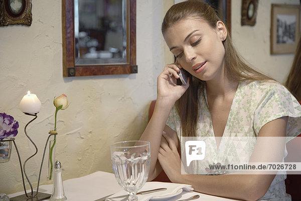 Handy  Frau  sprechen  am Tisch essen  Tisch