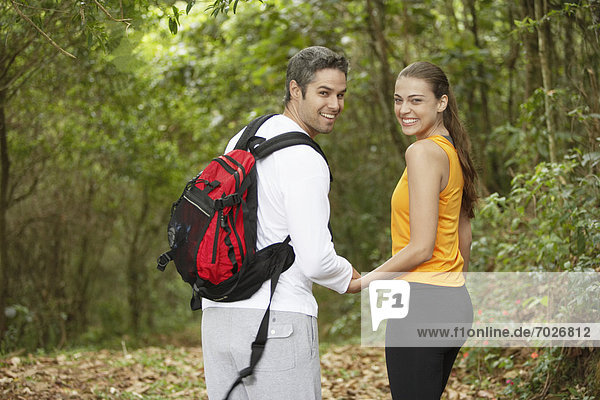 Couple holding hands in forest  rear view  portrait