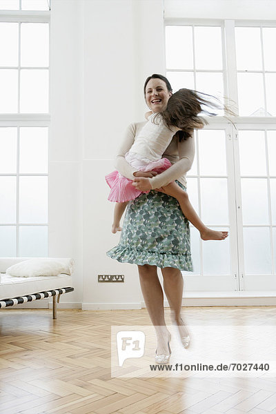 Mother carrying daughter in living room