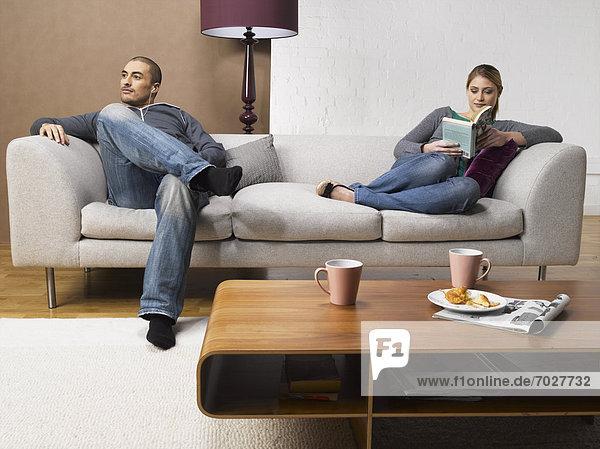 Frau  Mann  zuhören  Couch  Buch  Spiel  jung  MP3-Player  MP3 Spieler  MP3 Player  MP3-Spieler  Taschenbuch  vorlesen
