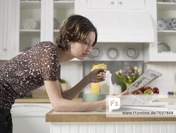 Frau  Küche  Mittelpunkt  Erwachsener  Frühstück  Tresen  Zeitung  vorlesen