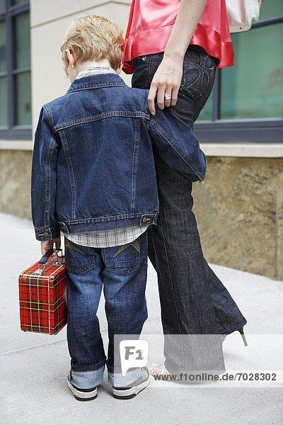 Boy holding mother's leg