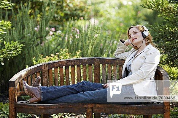 Young Woman Listening to Headphones in Garden