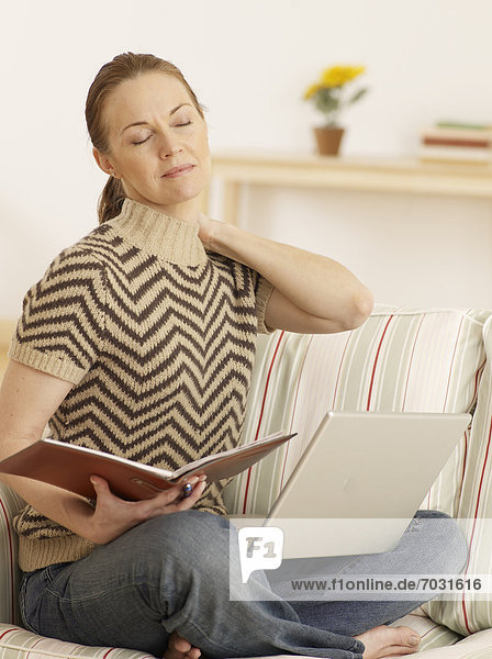 Mid-Adult Woman with Laptop and Notepad Stretching