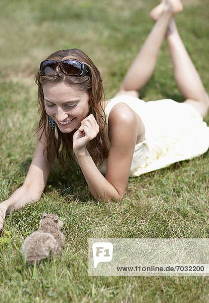 Mid-Adult Woman Looking at Rabbit on Lawn