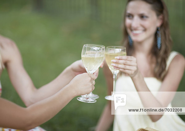 Three Women Toasting with White Wine