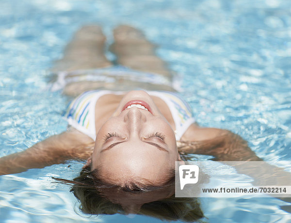 Mid-Adult Woman Floating in Swimming Pool